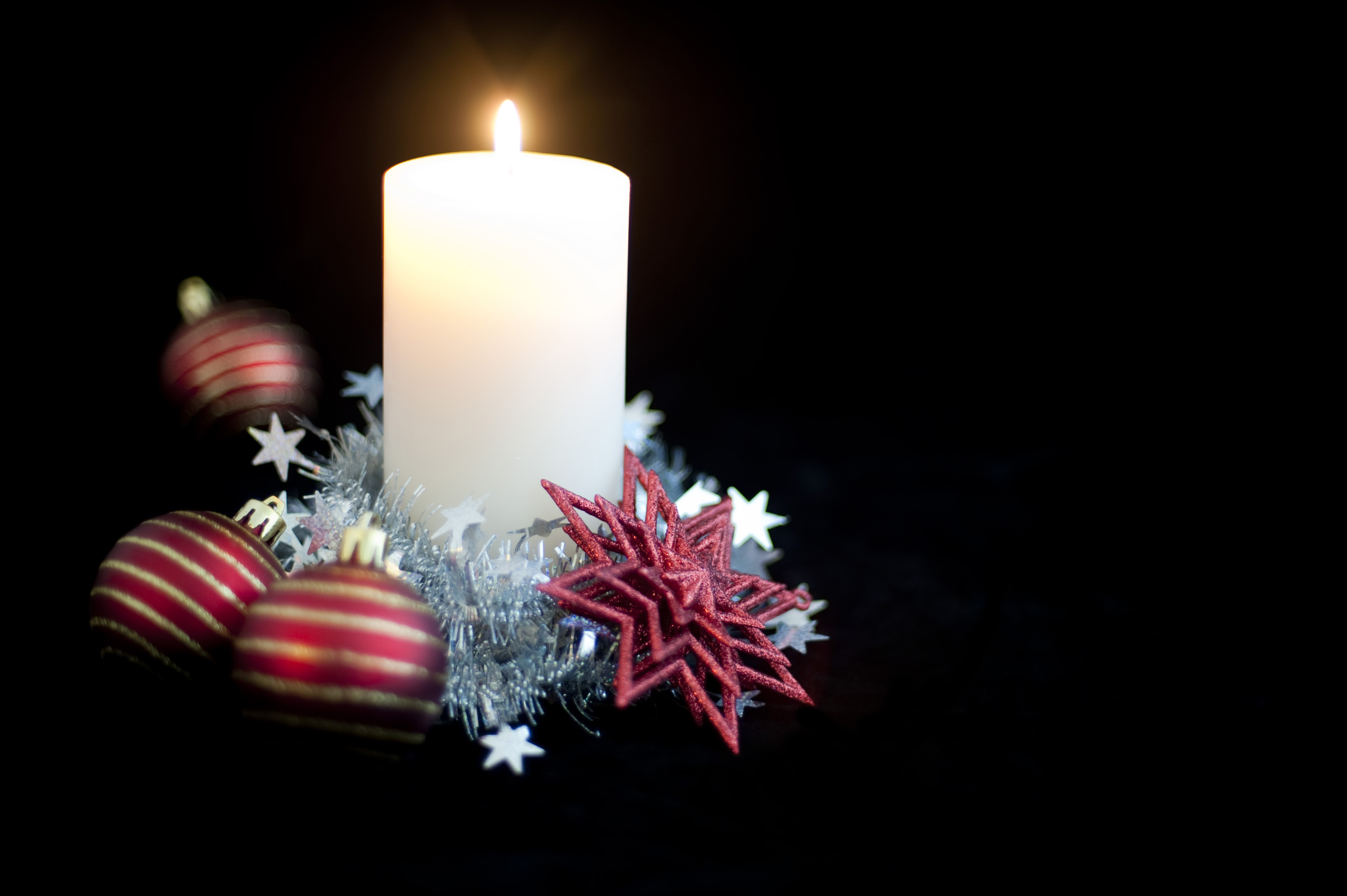 a christmas candle decorated with christmas balls and tinsel